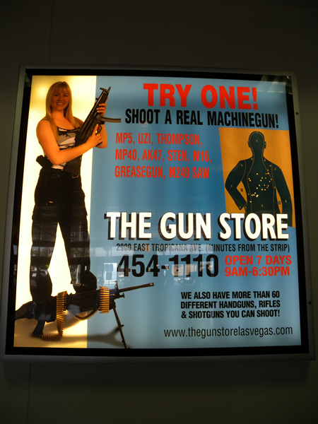 "Sign: ""Try One! Shoot a real machinegun! MP5, Uzi, Thompson, MP40, AK-47, Sten, M16, Greasegun, M249 SAW. The Gun Store"""