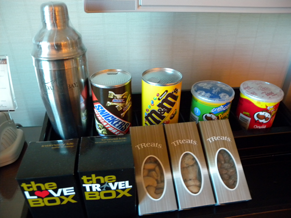 "Cocktail shaker, can of Snickers miniatures, can of M&Ms, can of sour cream and chives Pringles, can of original Pringles, 3 boxes of assorted nuts, ""The Love Box"" and ""The Travel Box"""