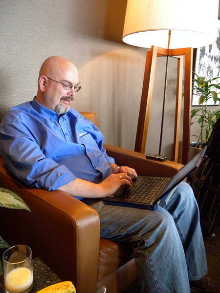Damir Bersinic working on his laptop in an easy chair in Vancouver airport's Air Canada lounge