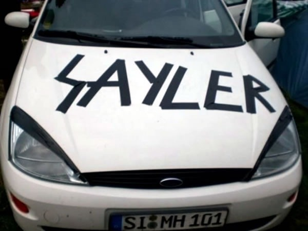 """White Ford Fiesta with """"SAYLER"""" spelled on its hood in black duct tape"""