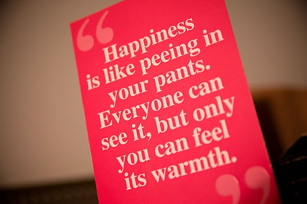 "Sign: ""Happiness is like peeing in your pants. Everyone can see it, but only you can feel its warmth."""