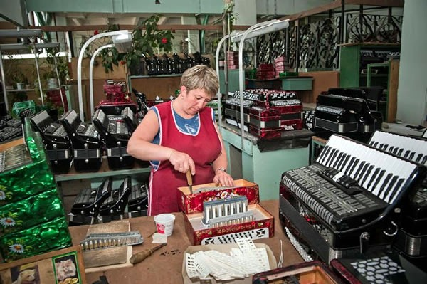 Woman assembling an accordion in a room full of them