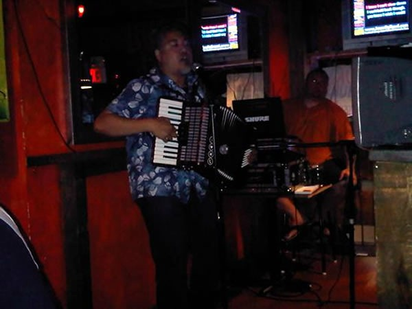 "Joey deVilla playing ""Ain't No Rest for the Wicked"" on accordion at Loser Karaoke with Jason Rolland in the background"