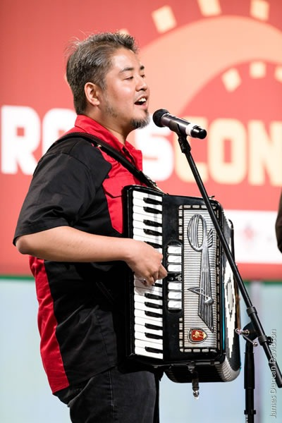 Joey deVilla playing accordion in front of the RailsConf logo