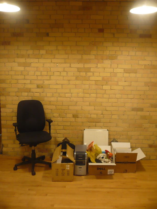 An office chair, a computer and some boxes lined up against an interior brick wall