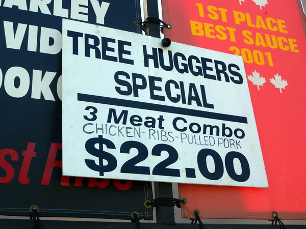 "Sign: ""Tree Huggers Special: 3 meat combo (chicken - rubs - pulled pork) $22.00"""