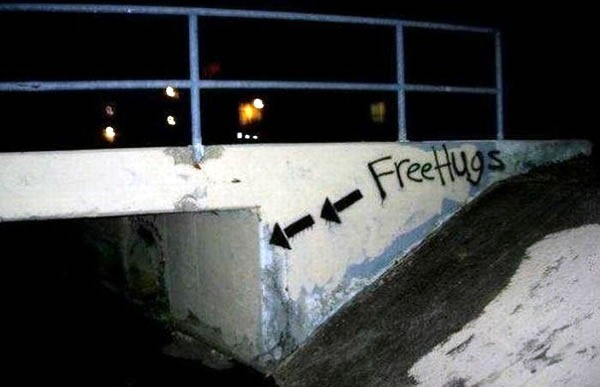 "Dark tunnel under a small footbridge labelled in spraypaint: ""Free hugs"""