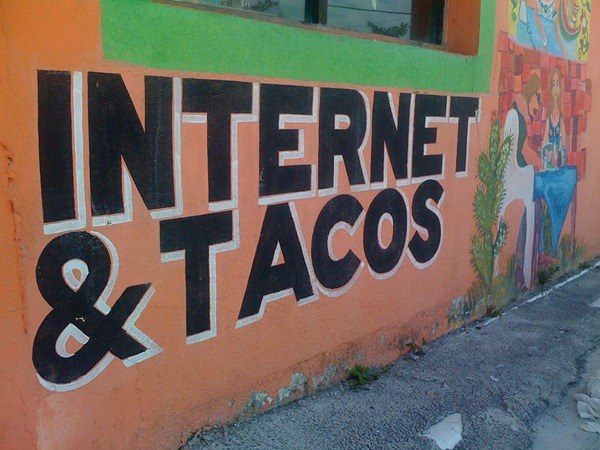 "Painted sign on an exterior wall: ""Internet & Tacos"""