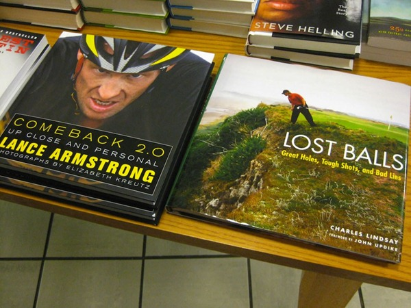 "Table at bookstore with a Lance Armstrong book places beside a book titled ""Lost Balls"""