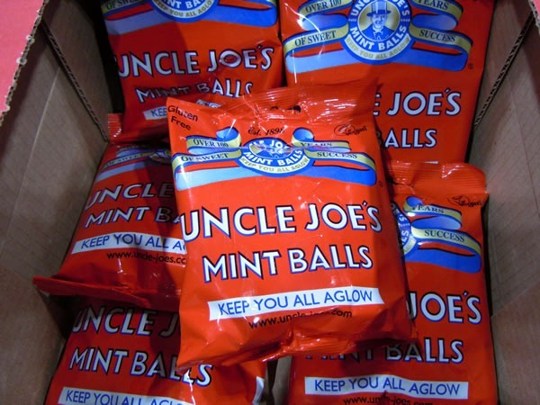 "Packages of ""Uncle Joe's Mint Balls"", which have the slogan ""Keep you all aglow"""