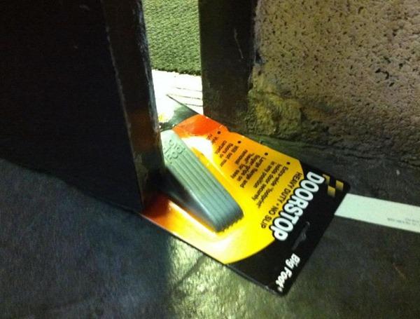 Doorstop, still in its packaging, being used to prop a door ajar