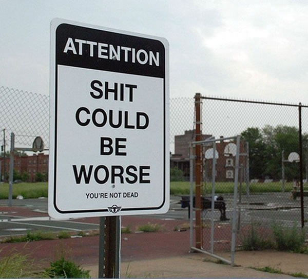 """Sign in a playground that reads """"Attention / Shit could be worse / You're not dead"""""""