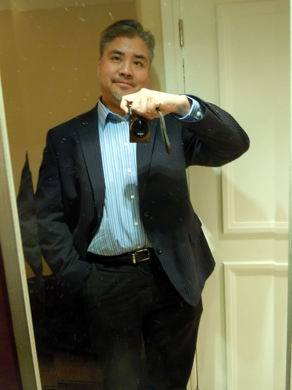 Joey deVilla, in a blazer, dress shirt and dress pants, taking a self-portrait in a mirror