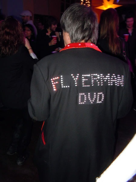 "Flyerman, from behind, with his trademark jacket studded with LEDs that spell out ""Flyerman DVD"""