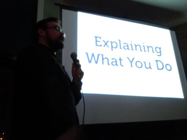 """Yehuda Katz giving his presentation with a slide in the background that reads """"Explaining What You Do"""""""