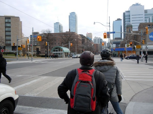 View from the eastbound bike lane at University Avenue and College street, with two cyclists ahead