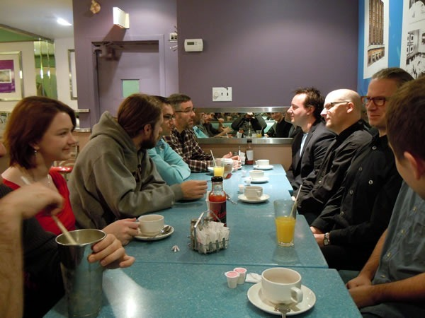A long booth at Fran's diner, with assorted Toronto nerds drinking coffee and conversing