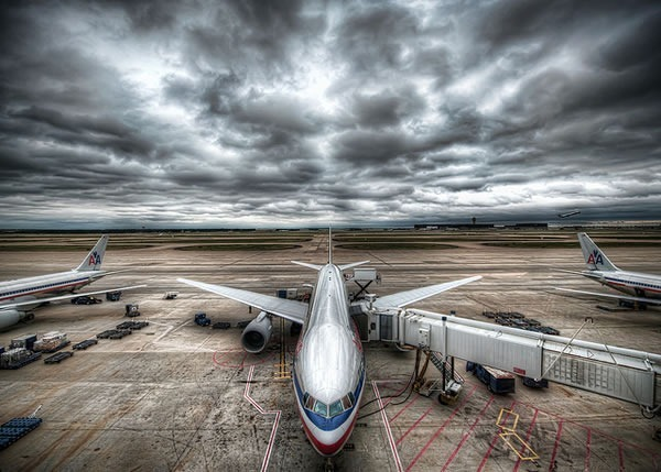 Airplanes on a tarmac under a cloudy grey sky