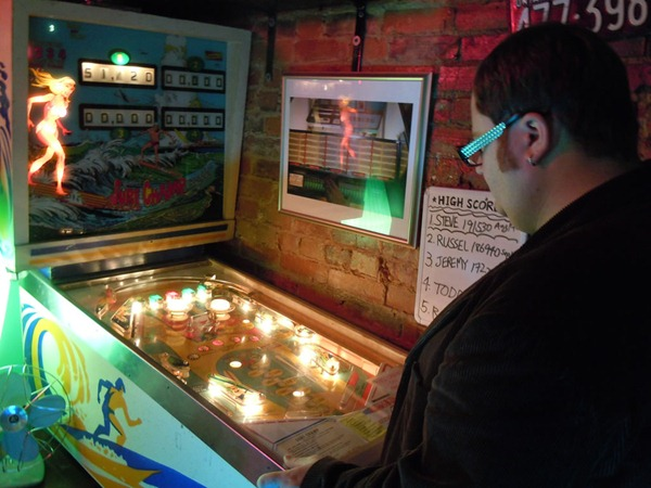 Pete playing pinball at the Black Dice Cafe