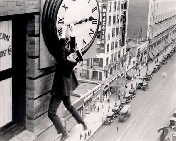 Buster Keaton hanging from the big hand of a building-mounted clock