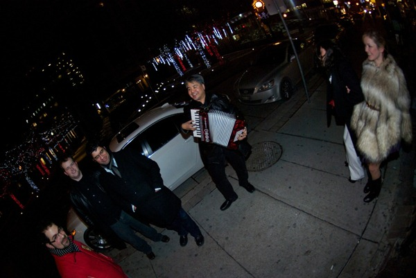 Joey deVilla plays accordion as his friends and two ladies passing by watch