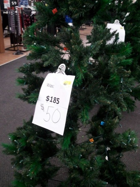 "Christmas tree with a sign that reads: ""Was $185 Now $50"""