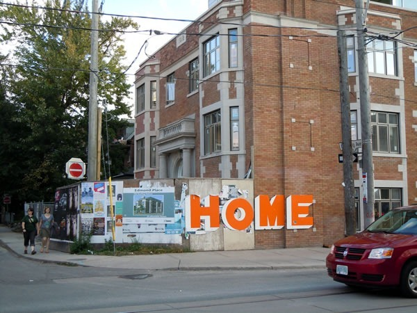 "An apartment building under renovation, surrounded by a construction wall with the word ""HOME"" painted on it in large orange letters"