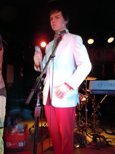 Sean Ward, in white jacket, red dress shirt and red pants