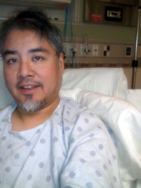 A scruffy and unshaven Joey deVilla lying in a hospital bed, wearing a hospital gown