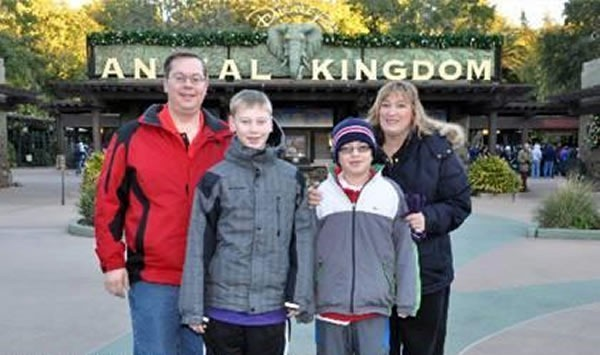"""Family posing in front of Disney's """"Animal Kingdom"""" sign, with Dad's head blocking the """"im"""" in """"Animal"""""""
