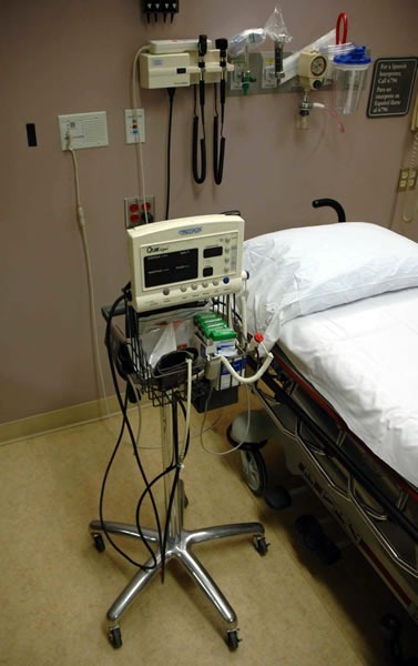 Automatic blood pressur cuff, poised beside an ER bed