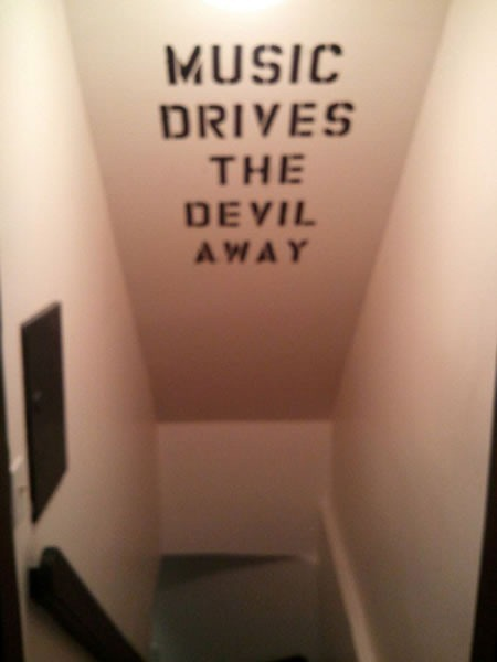"Stairwell leading down with ""MUSIC DRIVES THE DEVIL AWAY"" painted on the ceiling in stencil"