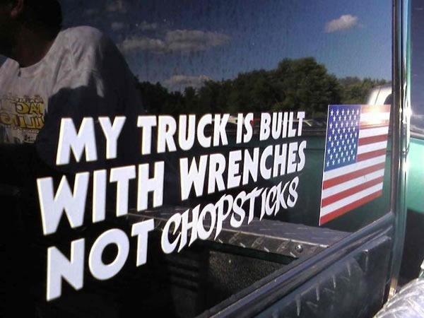 "Lettering on truck beside US flag: ""My truck is built with wrenches not chopsticks"""