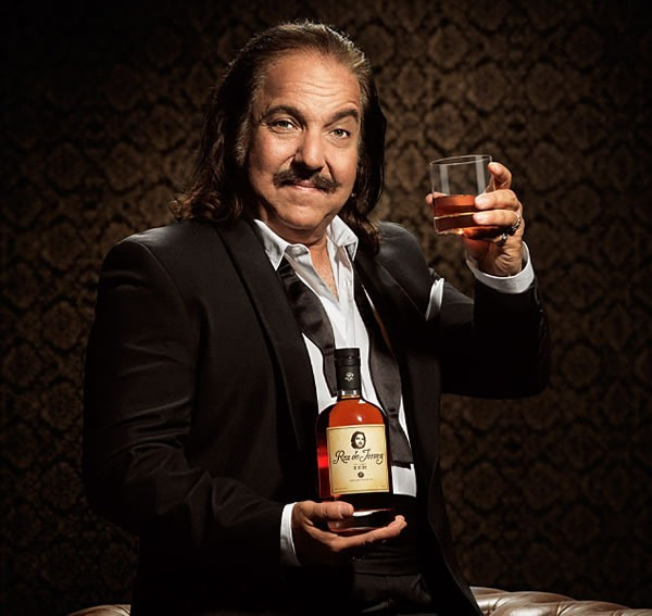 Ron Jeremy in a tuxedo (with top shirt buttons and bow tie undone), holding a bottle of Ron de Jeremy