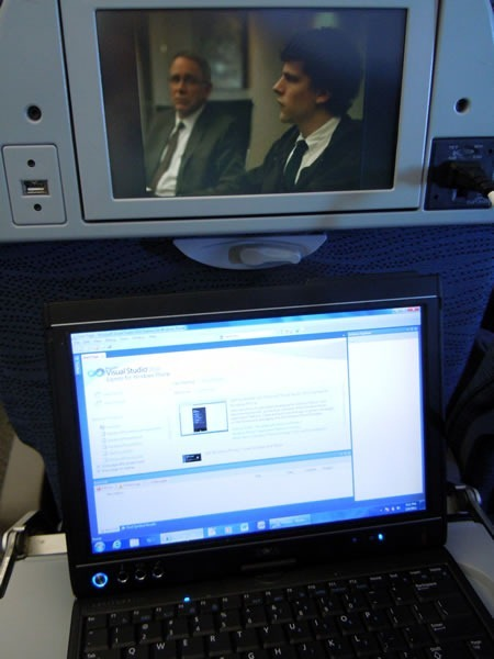 """The Social Network"" playing on in-flight entertainment system while I work on my laptop, with Visual Studio Express for Phone onscreen"