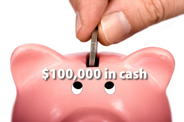 $100,000 in cash: close-up of a hand putting a coin in a piggy bank