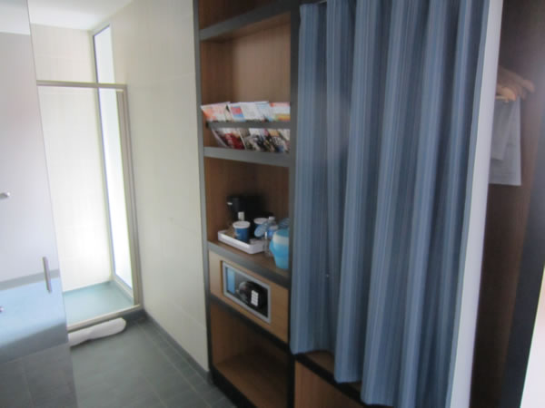 Closet area of the room, featuring curtained-off closet, magazine rack, coffee maker, ice bucket and safe