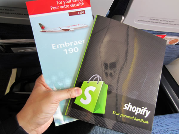 Me holding an Air Canada safety booklet and the Shopify Employee booklet