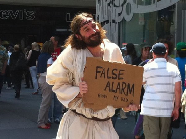 Guy dressed up as Jesus holding up a cardboard sign that reads