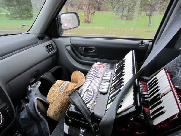 Front passenger seat of my car, with two accordions strapped in with the seatbelt.