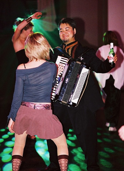 Photo of Joey deVilla dancing with a blonde woman who is fondling his accordion.