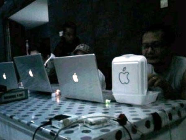 Three people working on Powerbooks with the Apple logo glowing on their cover, and one guy eating lunch from a styrofoam container with the Apple logo drawn on it in magic marker.