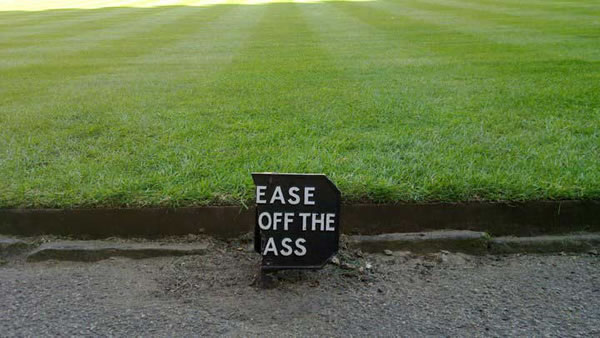 Park with 'Please keep off the grass' sign broken so that it now reads 'Ease off the ass'.