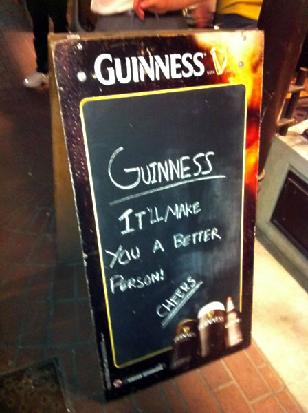 Photo: 'Sandwich board' sign that reads 'Guinness: It'll make you a better person!'
