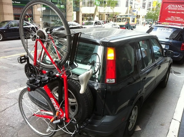 Joey's car (Black Honda CR-V), packed to the gills, with a red bike in the rear-mounted bike rack.