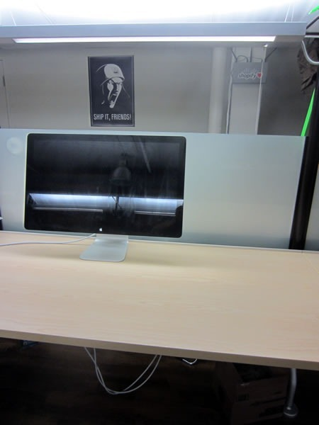 A desk that is empty except for an Apple monitor