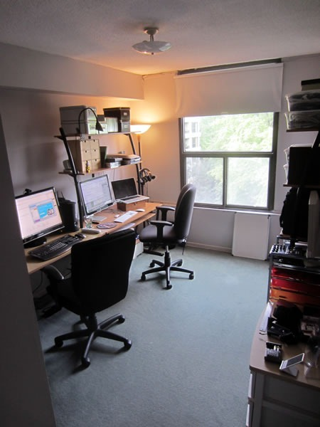 Carpeted apartment bedroom converted into a home office, showing a long desk with computers and a window looking out onto treetops