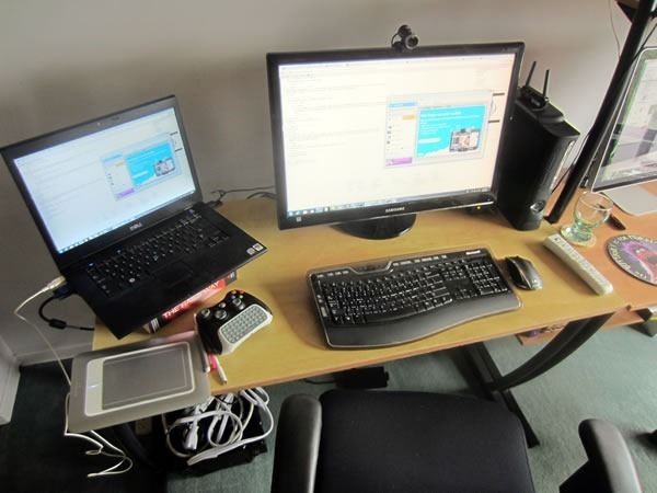 """The left side of Joey's workstation, with a Dell 15"""" laptop, 25"""" Samsung monitor, Wacom drawing tablet, Xbox and wireless controller and office chair"""