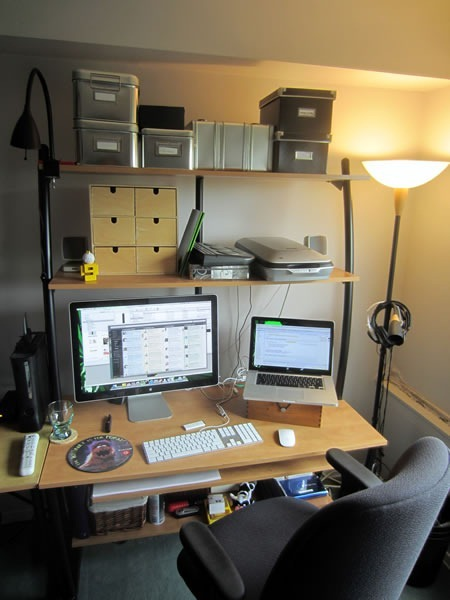 """The right side of Joey's workstation, showing a 15"""" Mackbook Pro, 24"""" Apple monitor, several organizing containers and a """"The Internet is for Porn"""" mousepad"""