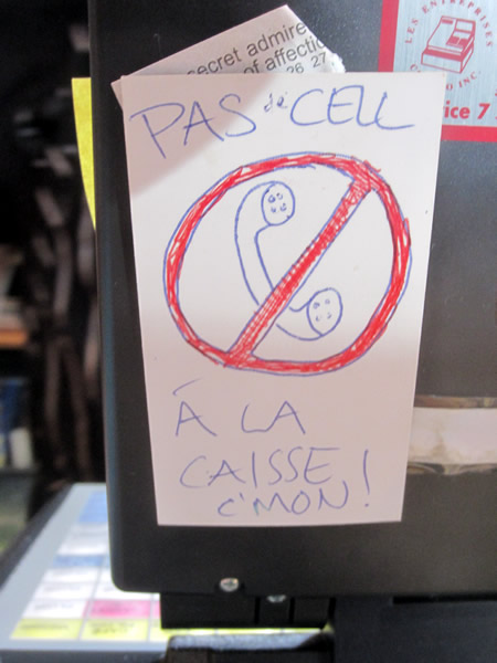 Photo of a notice taped to the customer-facing side of a cash register: 'Pas de cell a la caisse -- C'mon!